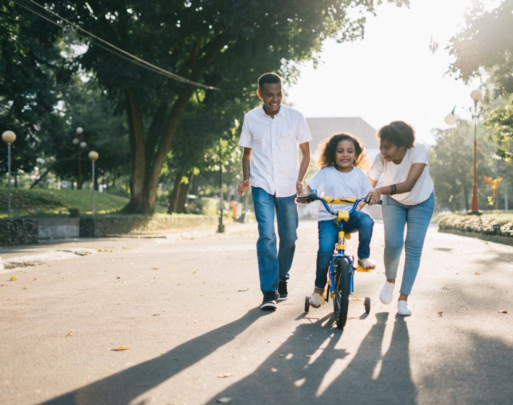 Child riding bike with her parents