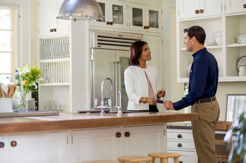 Two people standing in a kitchen