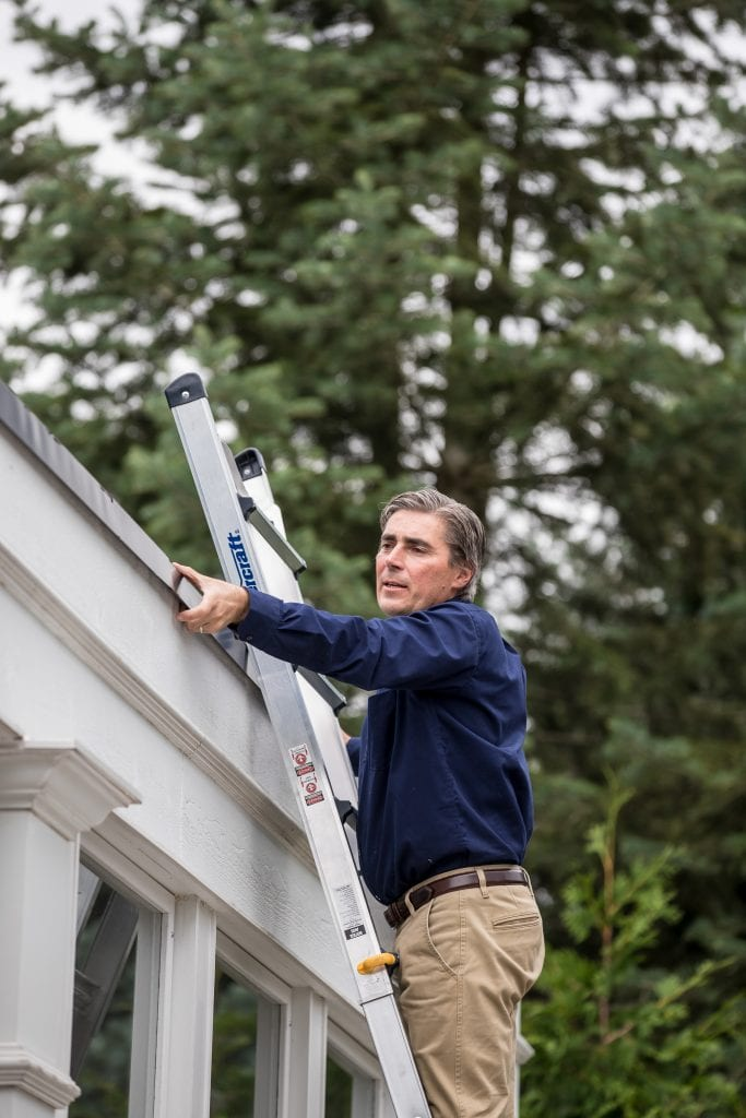 Man cleaning out gutters