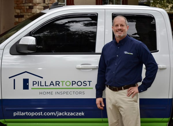 Jack Zaczek stands in front of his home inspection vehicle wearing a blue shirt and khaki pants