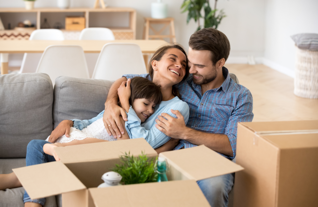 family sitting next to moving boxes